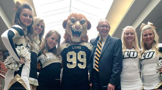 Photo from Day Admissions President Michael Shonrock gets to know Leo the Lion and members of the Lindenwood cheer team.