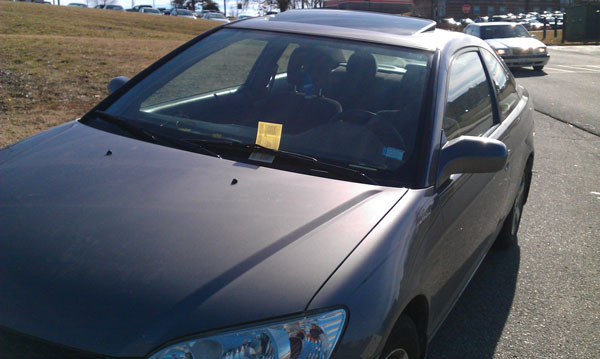 A stuent's car parked illegally outside of the Spellmann Center has a yellow ticket for the violation. Courtesy photo by Chandra Wood.