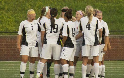 The women's soccer team huddles during a match.