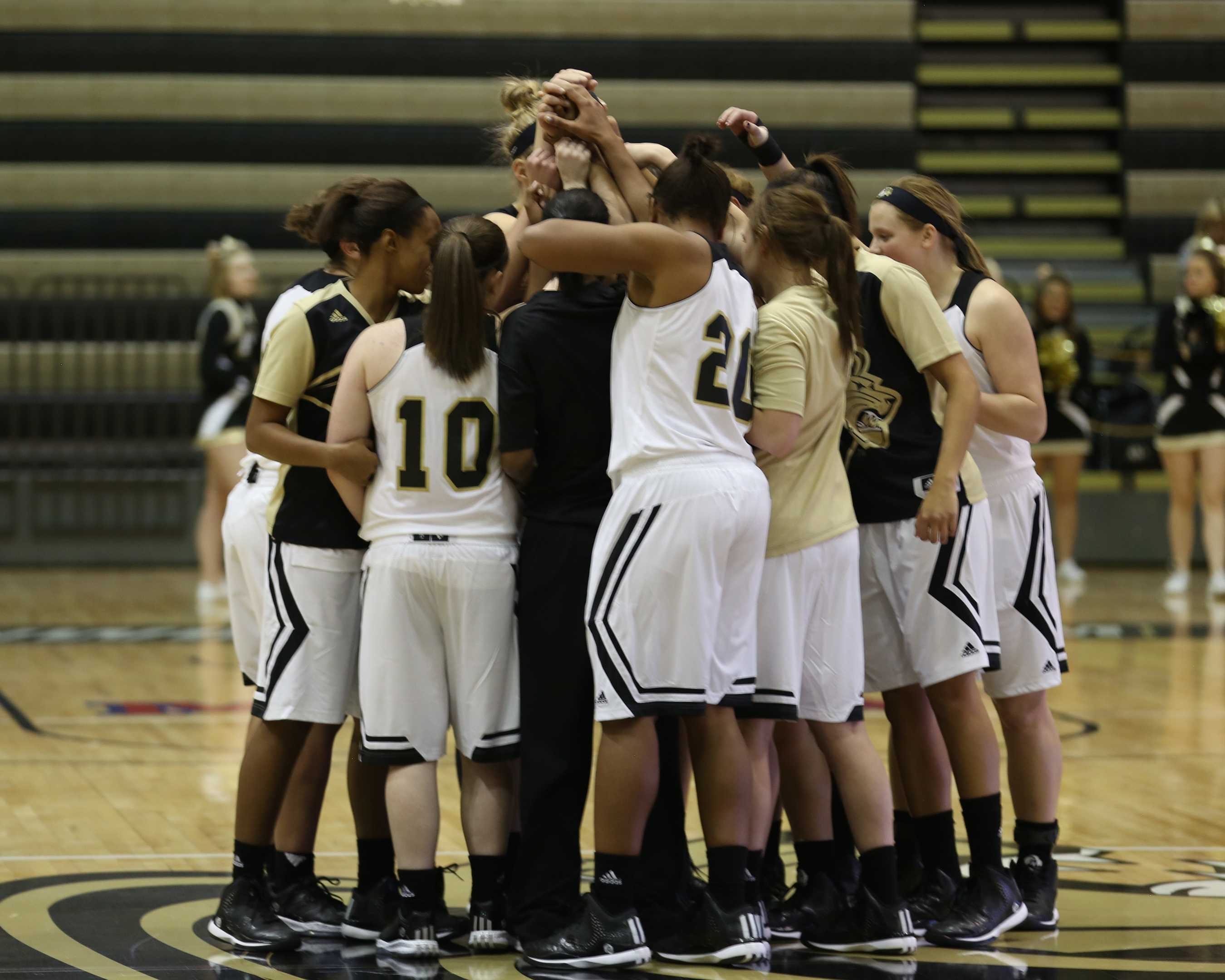 The women's basketball team huddles at center court during a game earlier this season.
