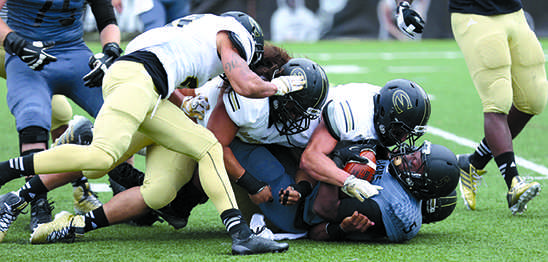 LU running back Lavorrie Johnson is tackled in the backfield by a group of Emporia State defenders during Sunday's game. <br> Photo by Carly Fristoe