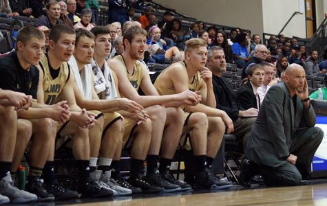 Lance Randall (right) kneels on the edge of the court as he watches his offense take on Lincoln University. <br />  Photo by Phil Brahm
