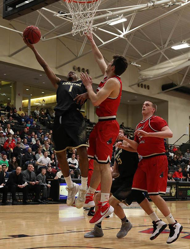 University of Central Missouri's Brad Woodson (3) and Jakob Lowrance (50) attempts to block Lindenwood's Brad Newman (1) as he goes for a layup.
