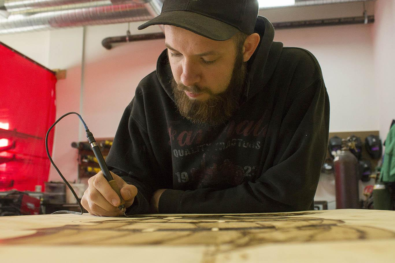 Photo by Sandro Perrino Graphic design major Zach Baker burns his pirate ship into a plank of wood, a hobby of his.