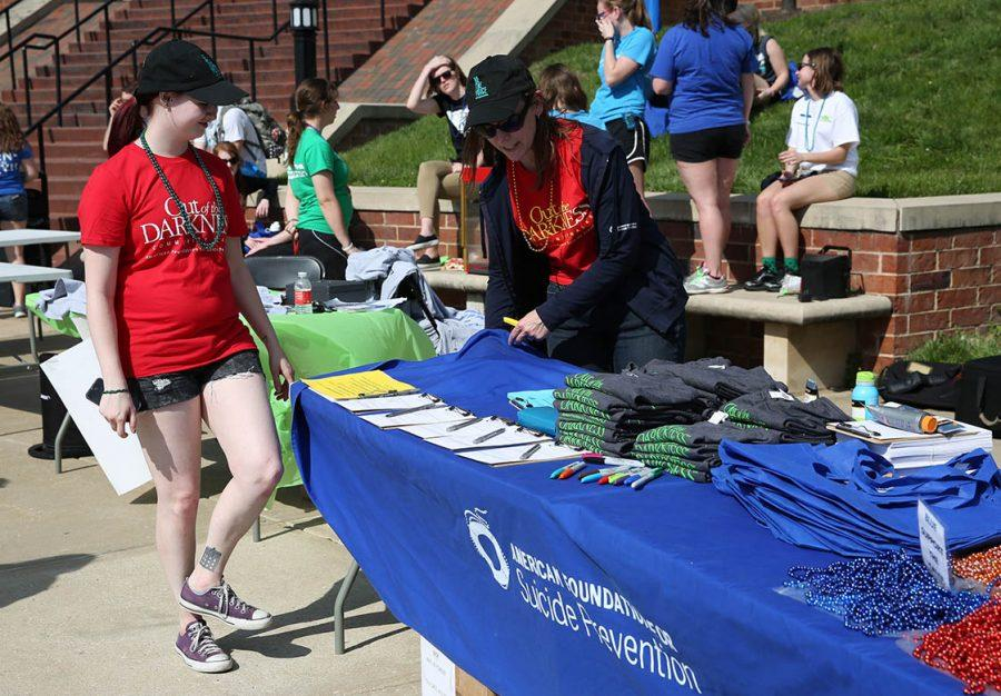 Photo by Ana Castillo Active Minds chapter president Amelia Fowler helps Liz Halpin set up at the starting point of the