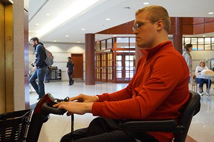Andrew Honerkamp waits for the elevator on the second floor of the Spellmann Center.  <br>Photo by Phil Brahm