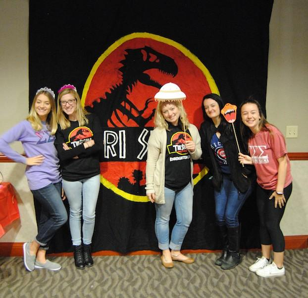 Tri+Sigma+members+Paige+Hirtz%2C+Lydia+Stewart%2C+Olivia+Stedman%2C+Emily+Saulnier%2C+and+Maggie+Wiltse+pose+in+front+of+the+dinosaur-themed+backdrop+with+photo+booth+props.+%3Cbr%3E+Photo+by+Madi+Nolte