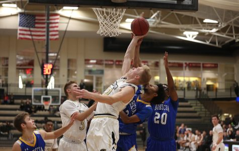 Chandler Diekvoss attempts a layup while being defended by two players from Brescia University. <br>Photo by Carly Fristoe</br>