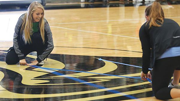 Miranda Heubner and Taylor Wade participate in a halftime game during a Lindenwood basketball game.  Photo by Carly Fristoe