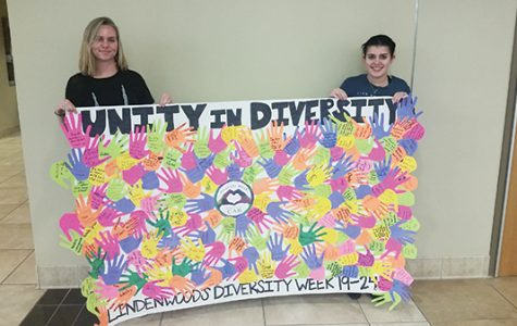 Campus Activities Board Event Coordinators Kayla Drake and T.J. Tipton hold the Diversity Week banner with different cut-out hands with people's comments on what makes them diverse.<br> Photo by Lindsey Fiala