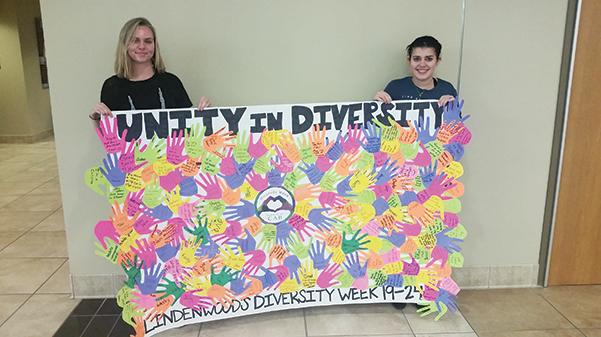 Campus+Activities+Board+Event+Coordinators+Kayla+Drake+and+T.J.+Tipton+hold+the+Diversity+Week+banner+with+different+cut-out+hands+with+people%E2%80%99s+comments+on+what+makes+them+diverse.%3Cbr%3E%0APhoto+by+Lindsey+Fiala