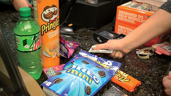 A student purchases a wide array of 'junk food' with her dining dollars in the convenience store on the second floor of the Spellmann Center.<br>Photo Illustration by Kelby Lorenz