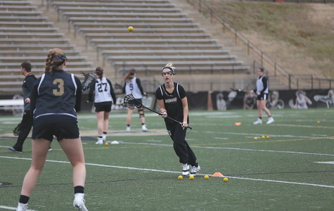 Senior Sarah Goetz keeps her eye on the ball coming to her from sophomore teammate Sarah Cromer during a spring practice in Hunter Stadium. </br>  Photo by Carly Fristoe