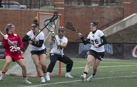Senior Molly Beckham (26) and freshman Alana Jeronimo (51) guard  Lindenwood's goal in front of  freshman goalkeeper Aly Smith (11).<br>Photo by Kelly Logan