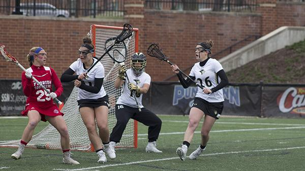 Senior Molly Beckham (26) and freshman Alana Jeronimo (51) guard Lindenwood's goal in front of freshman goalkeeper Aly Smith (11). Photo by Kelly Logan