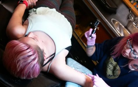 Michelle Sproat gets her first tattoo from artist Katy Raymon at Iron Age Tattoo while holding Jacob Jagodzinski's hand.<br>Photo from Michelle Sproat