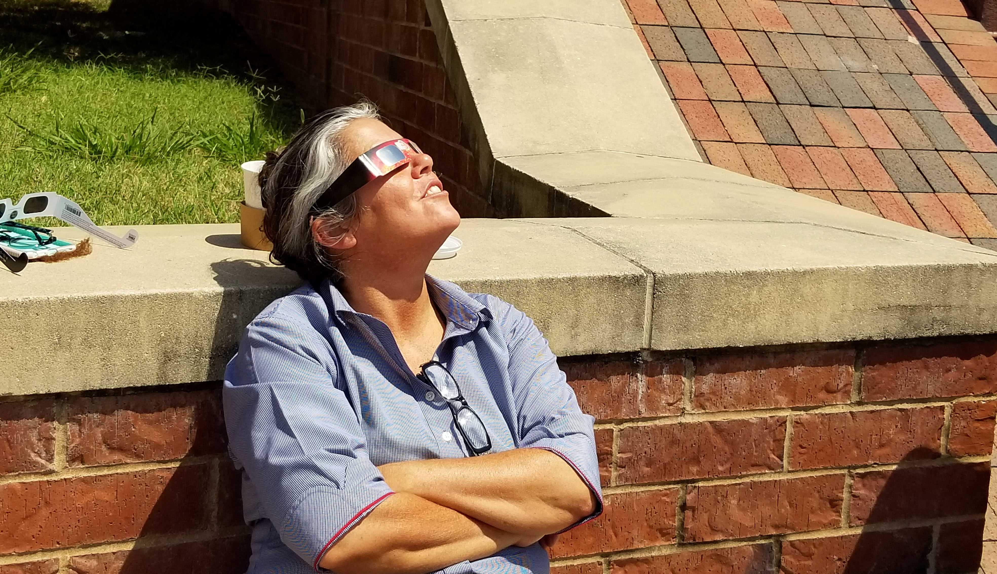Angie Siebert, general manager at the Lindenwood campus Chick-fil-A, looks up at the partial solar eclipse that occurred over Missouri on Monday. Photo by Michelle Sproat.