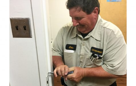 Maintenance worker John Robin fixes a door in Parker Hall that has trouble locking. <br> Photo by J.T. Buchheit