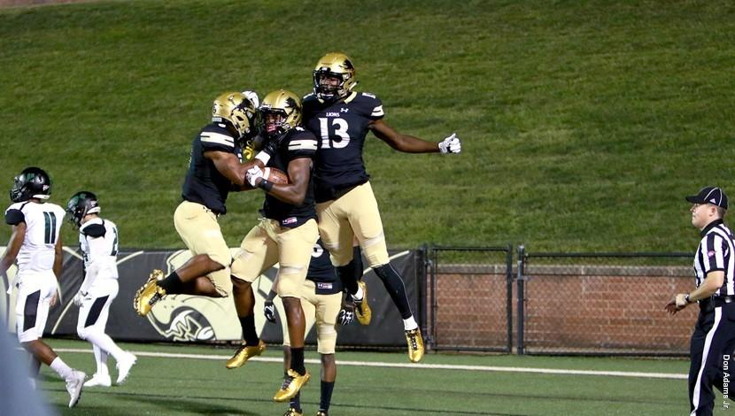 Justin Smith and two other Lindenwood Lions player jump into the air to celebrate a Lindenwood touchdown against Northeastern State University at Hunter Stadium on Sept. 7. Lindenwood won 49-10.  Photo by Lindenwood Athletics