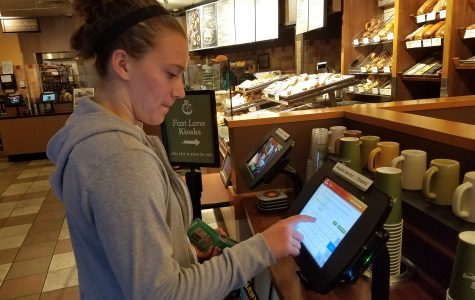 Sophomore Ariana Fischer uses the self-checkout counter at St. Louis Bread Company. <br> Photo by Kayla Drake