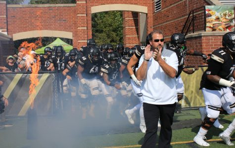 Head coach Jed Stugart claps as the football team runs onto the field before the Homecoming game.  <br> File photo by Lindsey Fiala
