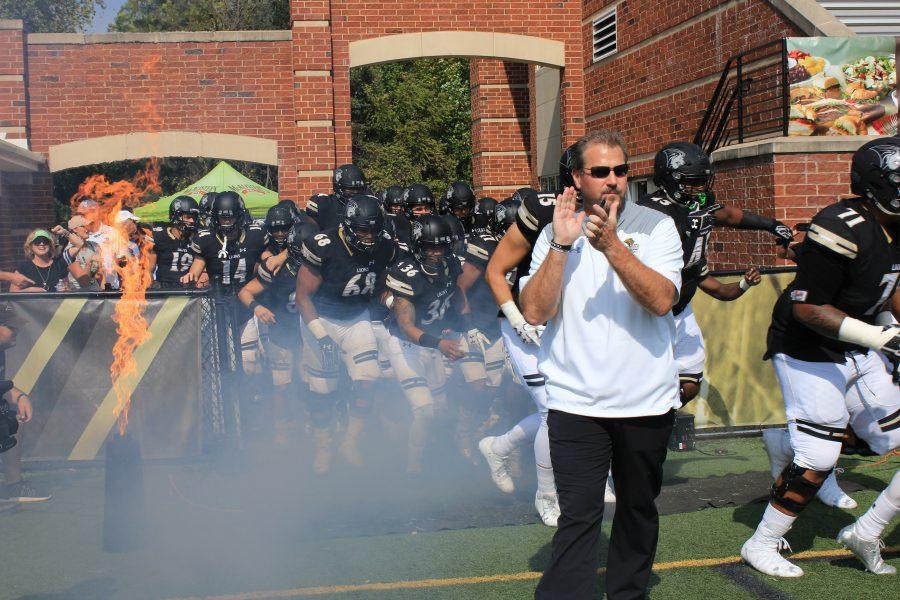 Head coach Jed Stugart claps as the football team runs onto the field before the Homecoming game.   File photo by Lindsey Fiala