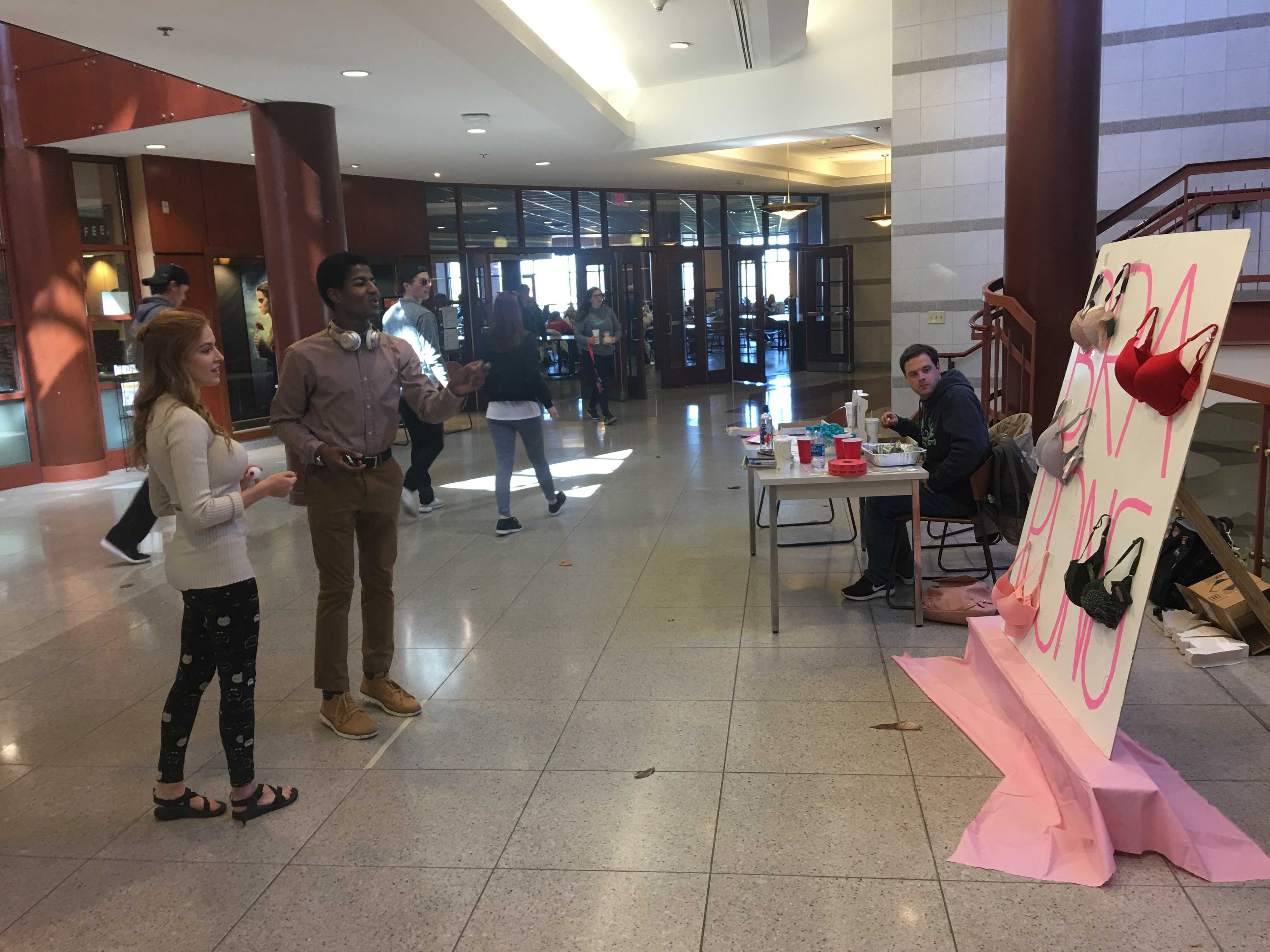 Delta Zeta member Jessie Basler assists junior Ashraf Ahmed as he tries to throws ping pong balls into bras Oct. 25 in Spellmann Center. Delta Zata and Delta Tau Delta joined up to raise funds for breast cancer research with the bra pong game.  Photo by Ciara Griffin
