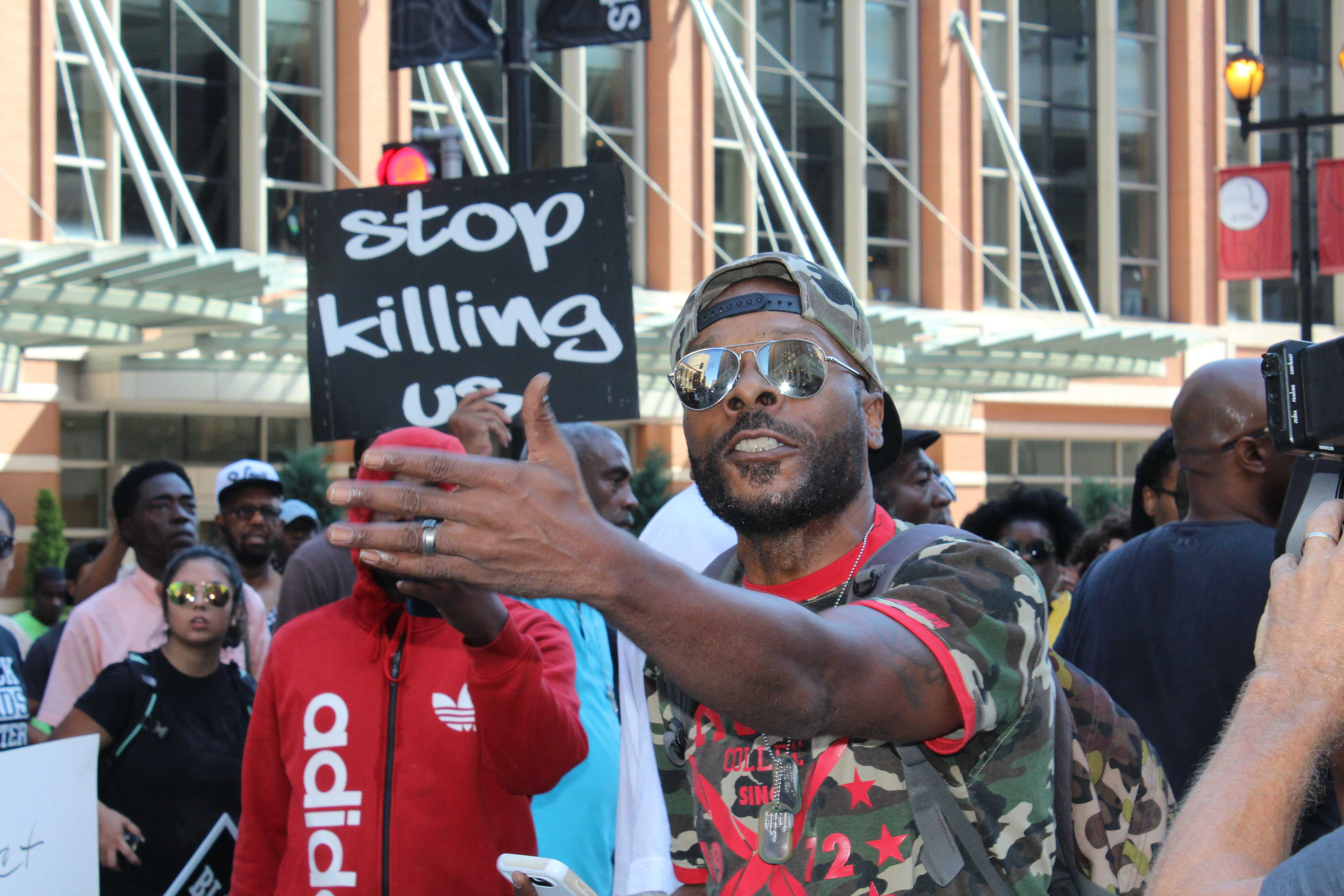 """Left: Protester Kevin Nevels speaks loudly about personal encounters with police. """"Every time a police pulls up behind me, I have to grab my steering wheel. Do white people?"""""""
