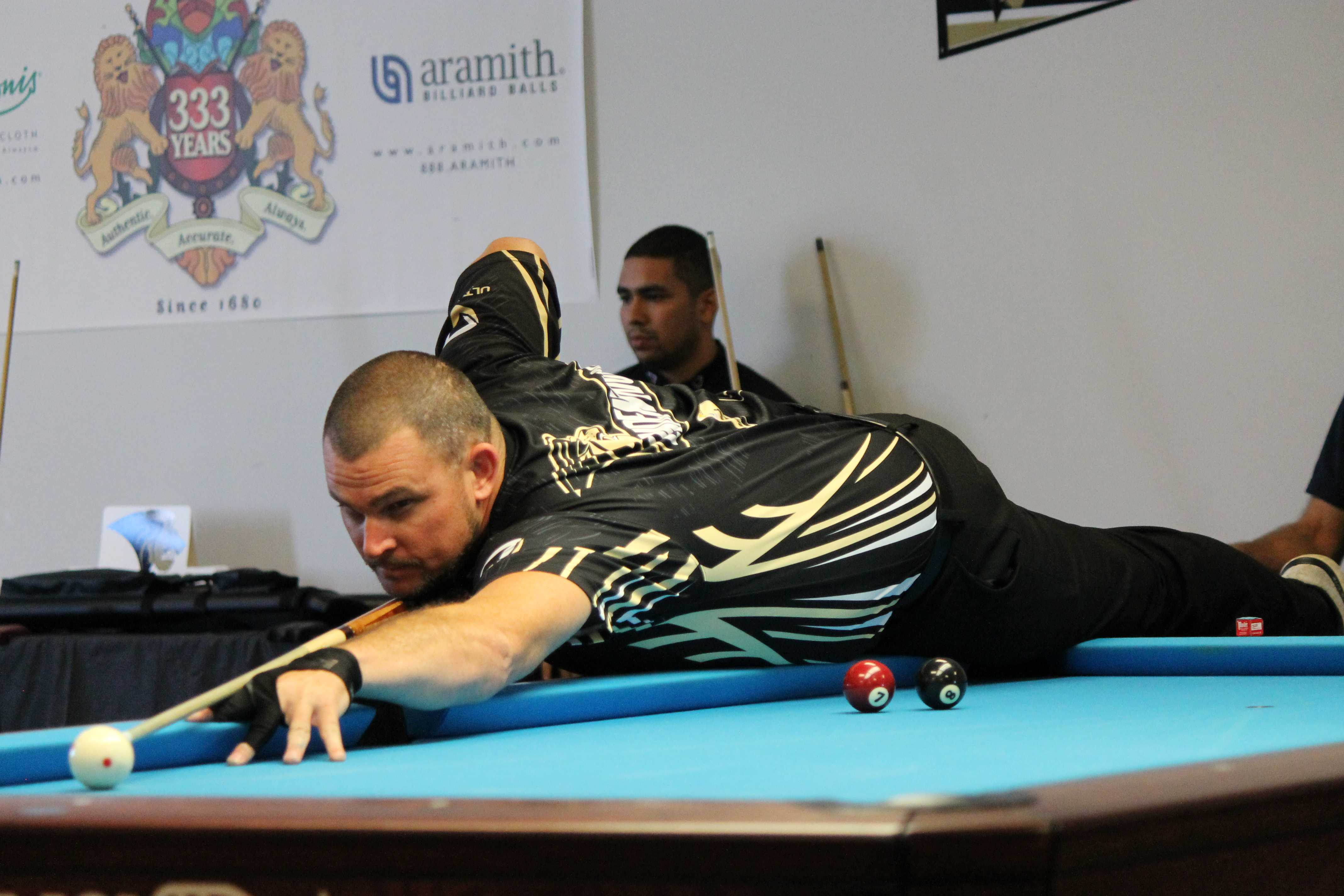 Brandon Jordan stretches across the table during the first set of his two win tournament.  Photo by Walker Van Wey