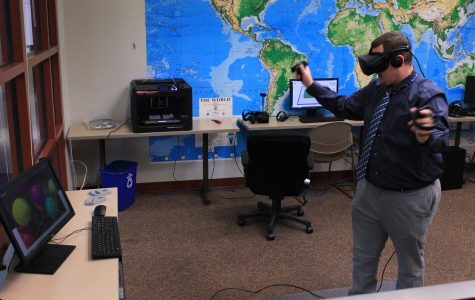 Adjunct professor Chris Pusczak tests the new equipment in the test virtual-reality studio in Spellmann 4085. <br> Photo by Lindsey Fiala.