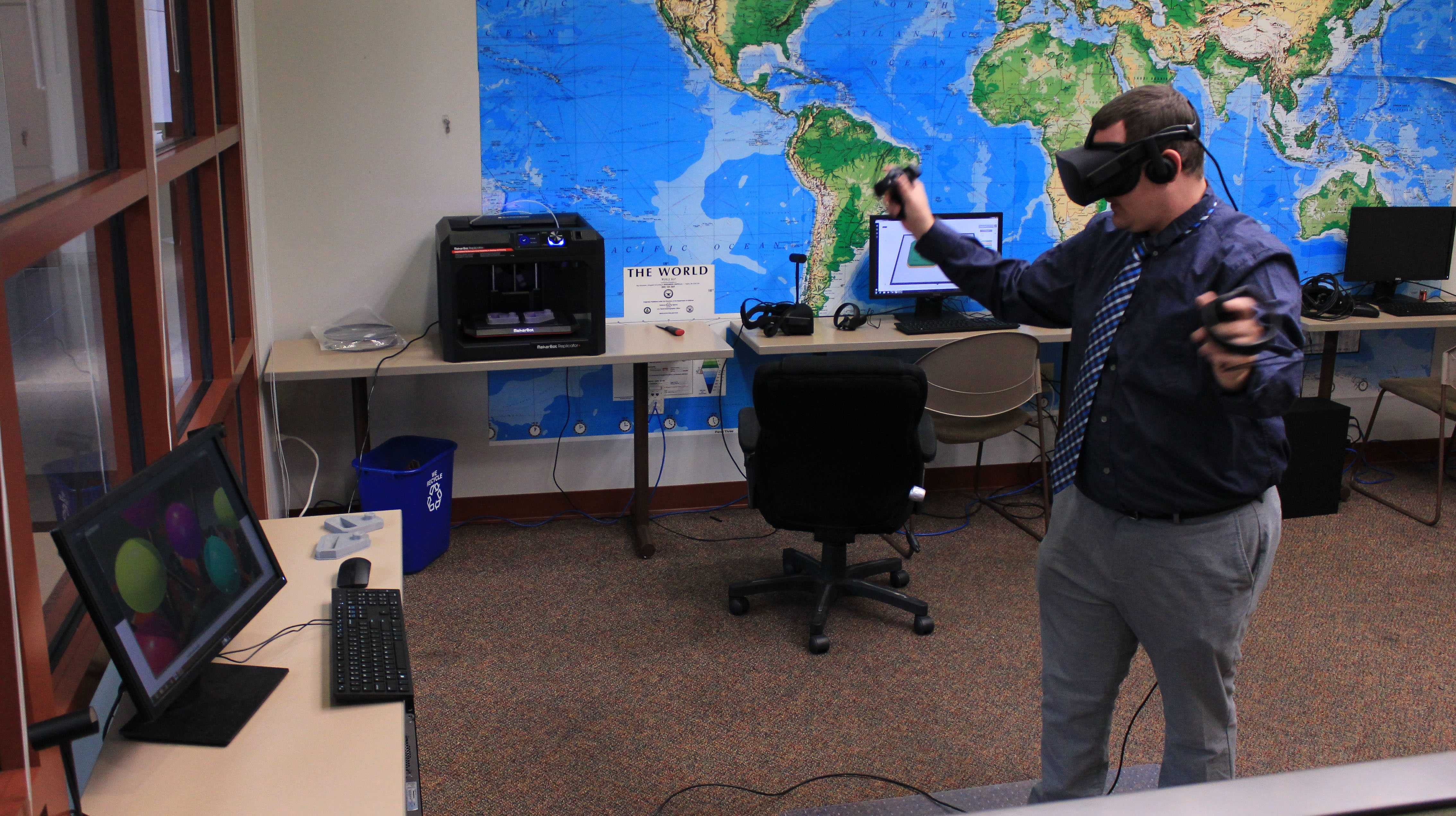 Adjunct professor Chris Pusczak tests the new equipment in the test virtual-reality studio in Spellmann 4085.  Photo by Lindsey Fiala.