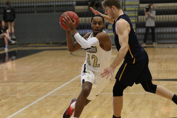 Guard+Brad+Newman%2C+No.+12%2C+drives+to+the+basket+against+Beloit+College.+Newman+led+all+scorers%2C+with+19+points%2C+in+the+Lions%27+83-58+win+on+Nov.+28+in+Hyland+Arena.+%3Cbr%3E+Photo+by+Walker+Van+Wey