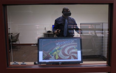 Adjunct instructor Chris Pusczak demonstrates how to play a game with a virtual-reality headset. These headsets will be used in classes for the game design major.  <br> Photo by Lindsey Fiala