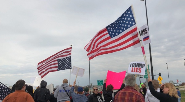 "Anti-Trump protesters stood on the street and sidewalks outside the St. Charles Convention Center on Nov. 29 to protest his tax plan proposal. Protesters waved upside down flags and held signs and chanted things like ""We want a leader, not a crazy tweeter."" Photo by Madeline Raineri."