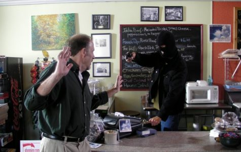 (left) A masked Benet Schaeffer holds former Lindenwood student Greg Hunsaker at gunpoint during a scene of