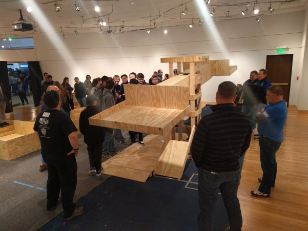 FIRST+Robotics+competitors+examine+a+scale+model+of+the+mechanism+they+will+have+to+use+in+six+weeks+at+the+regional+competition.+Photo+by+Mitchell+Kraus