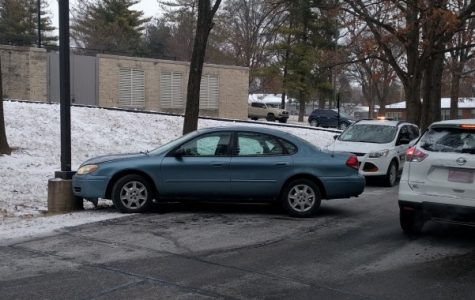 A light blue Ford Taurus rests against a pole near the north end of Evans Commons. <br> Photo by Mitchell Kraus