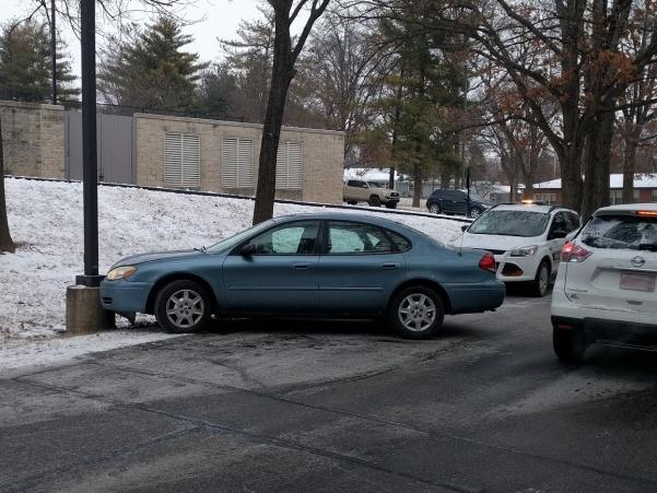 A+light+blue+Ford+Taurus+rests+against+a+pole+near+the+north+end+of+Evans+Commons.++Photo+by+Mitchell+Kraus