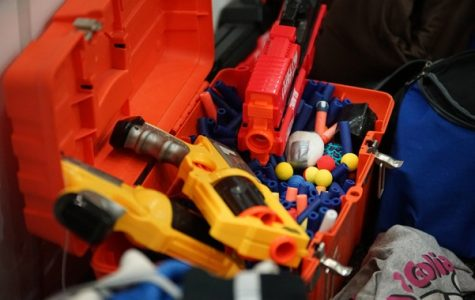 A bucket of Nerf blasters and darts sits in the sidelines. Regular participants often bring extra equipment to events so that new players can join in. <br> Photo by Mitchell Kraus