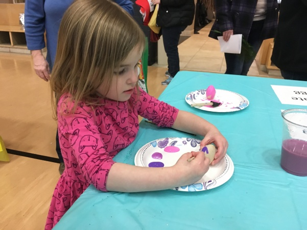 Lydia, age 7, decorates eggs at the Phi Sigma Sigma booth.  Photo by Arin Froidl