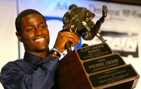 Pierre Desir holds up the Cliff Harris award in 2013. The award is given to the best small school defensive player in the country. <br/> Photo from Wikimedia Commons.