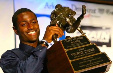 Pierre Desir holds up the Cliff Harris award in 2013. The award is given to the best small school defensive player in the country.  Photo from Wikimedia Commons.