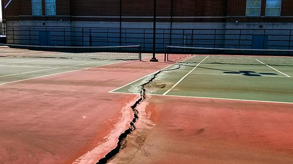 The tennis court directly next to the Hyland Arena has seen better days. Instead of leaving the eyesore as is, the space should be renovated as an outdoor basketball court.  Photo by Michelle Sproat.