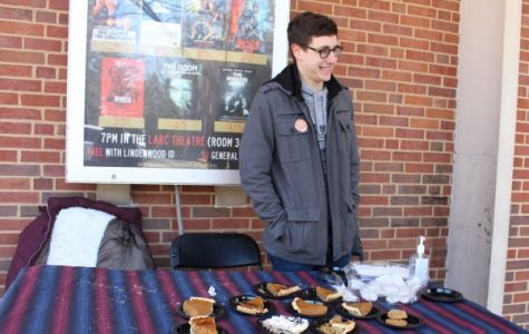 Dillon Bys, vice president of the Mathematics club sets up a table with free pies and buttons outside of Young. The Mathematics Club celebrated Pi Day or 3.14 day early because Pi Day falls on spring break this year. <br> Photo by Abby Stone