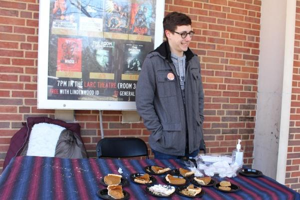 Dillon Bys, vice president of the Mathematics club sets up a table with free pies and buttons outside of Young. The Mathematics Club celebrated Pi Day or 3.14 day early because Pi Day falls on spring break this year.  Photo by Abby Stone