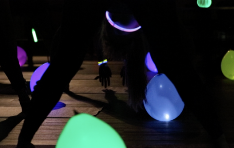 Students bend and touch the ground to stretch during Glowga in Butler Hall on April 24. <br> Photo by Kayla Drake. </br>