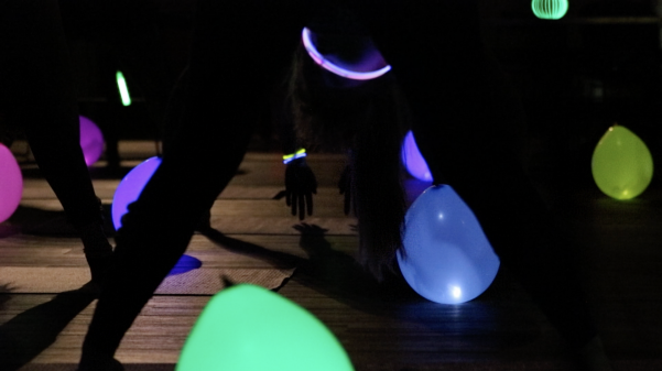 Students bend and touch the ground to stretch during Glowga in Butler Hall on April 24.  Photo by Kayla Drake.
