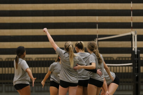 Athletes Hanna McGlockton (left), Sarah Stretch, Regan Ainsley and Jenna Garrett gather to celebrate as they win a point in a practice match on Wednesday, Sept. 12 at Hyland Arena.  Photo by Mina San Nicolás