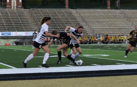 Junior Sammi Gregory (11) and sophomore Alaina White struggle for possession with Missouri Western forward Kelsey Burkey during the game on Sept. 14. Gregory tallied four shots for the Lions in the match.  <br /> Photo by Maria Escalona.