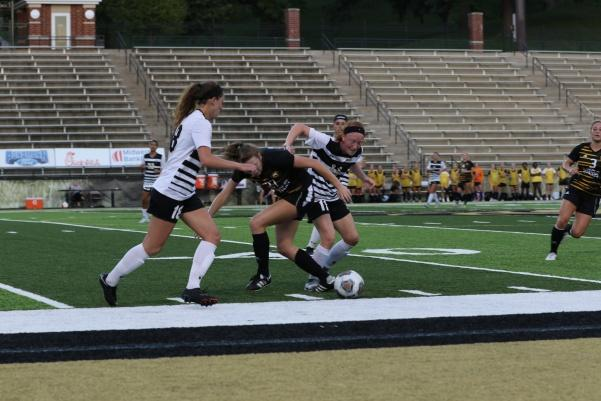 Junior Sammi Gregory (11) and sophomore Alaina White struggle for possession with Missouri Western forward Kelsey Burkey during the game on Sept. 14. Gregory tallied four shots for the Lions in the match.   Photo by Maria Escalona.